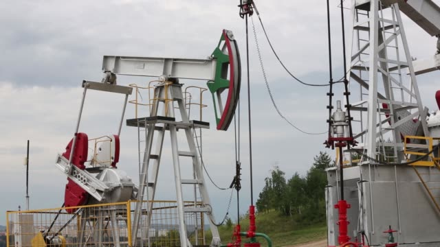 oil pumping units also known as nodding donkeys or pumping jacks stand on an oilfield operated by tatneft oao near residential housing in almetyevsk... - drill stock videos & royalty-free footage
