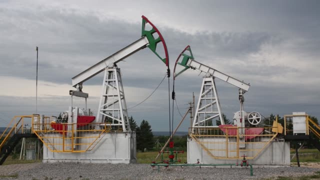 """vídeos de stock e filmes b-roll de oil pumping units, also known as """"nodding donkeys"""" or pumping jacks, stand on an oilfield operated by tatneft oao near residential housing in... - bomba petrolífera"""