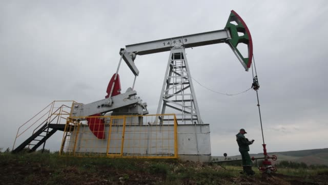 """oil pumping units, also known as """"nodding donkeys"""" or pumping jacks, stand on an oilfield operated by tatneft oao near residential housing in... - incomplete stock videos & royalty-free footage"""