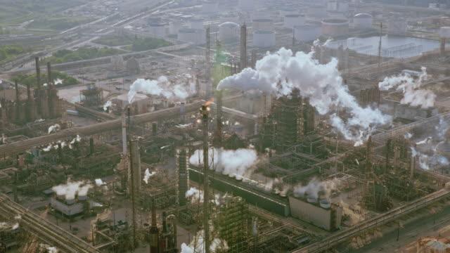 aerial ölraffinerie sind in texas mit türmen, die rauchschwaden ausstoßen - texas stock-videos und b-roll-filmmaterial