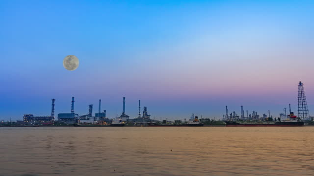 Oil refinery factory at full moon