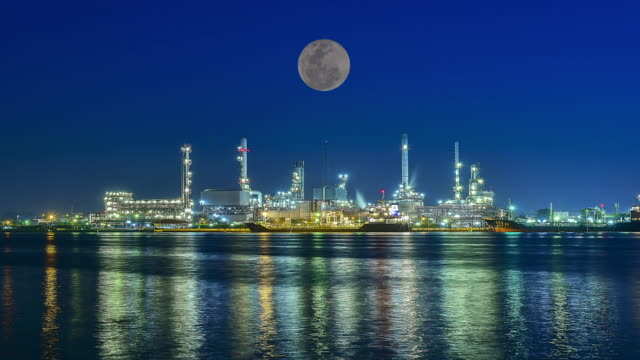 oil refinery factory at full moon - attrezzatura industriale video stock e b–roll