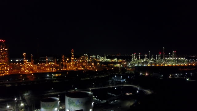 vídeos de stock e filmes b-roll de oil refinery plant form industry zone, aerial view oil and gas industrial, refinery factory oil storage tank and pipeline steel at night. - fábrica petroquímica
