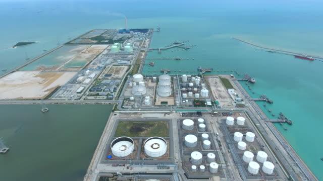 vídeos de stock e filmes b-roll de oil refinery plant near ocean in aerial view - refinaria de petróleo