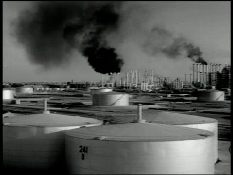 oil refinery smoke stack w/ black smoke round tanks fg - 1951 stock videos & royalty-free footage