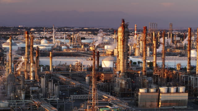 oil refinery steaming and glowing at sunset - drone shot - oil industry stock videos & royalty-free footage