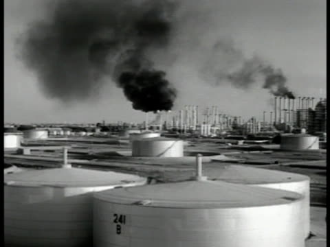oil refinery w/ train moving on tracks fg xws refinery w/ storage tanks fg ws refinery smoke stacks black smoke refinery entrance - 1951 bildbanksvideor och videomaterial från bakom kulisserna