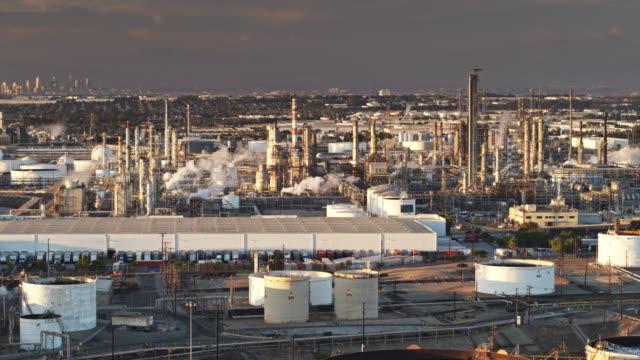 vídeos de stock e filmes b-roll de oil refinery warehouse with urban sprawl and dtla skyline in distance - drone shot - wilmington cidade de los angeles