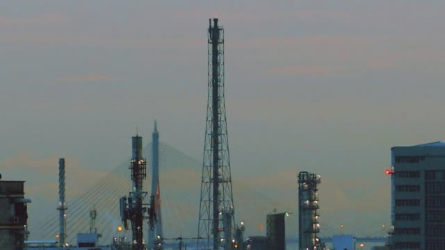 oil refinery with cityscape at sunset. - oil rig supply ship stock videos and b-roll footage