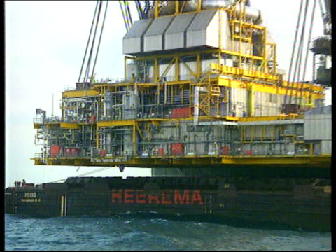 MS Legs of platform in sea with huge crane carrying superstructure in b/g CMS Superstructure suspended from crane PULL OUT MS Barge supporting...