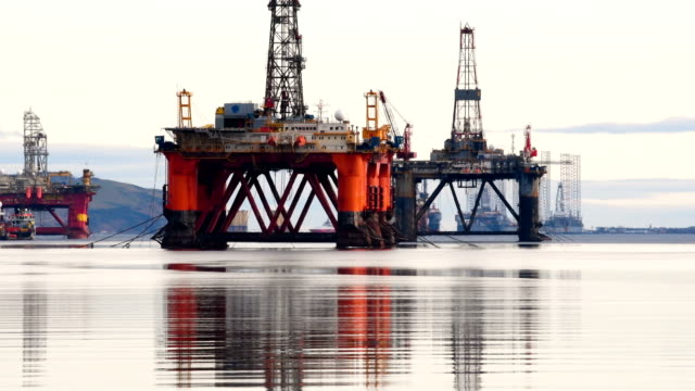 oil rigs weighing thousands of tons are continuing to be stacked up in the cromarty firth on january 12 2018 in invergordon scotland rig platforms... - trivella petrolifera video stock e b–roll