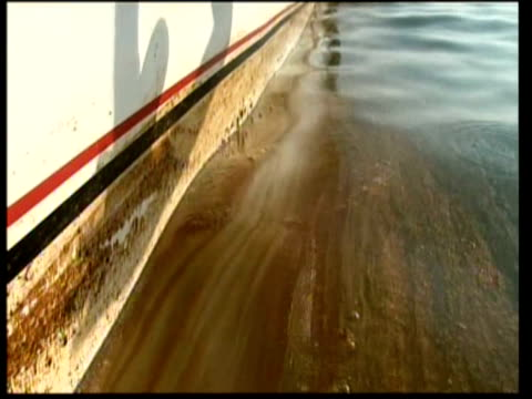 oil scum in water and on side of boat as hand collects sample in bottle / fishing boat at sea. gulf of mexico oil spill on may 06, 2010 - oil slick stock videos & royalty-free footage