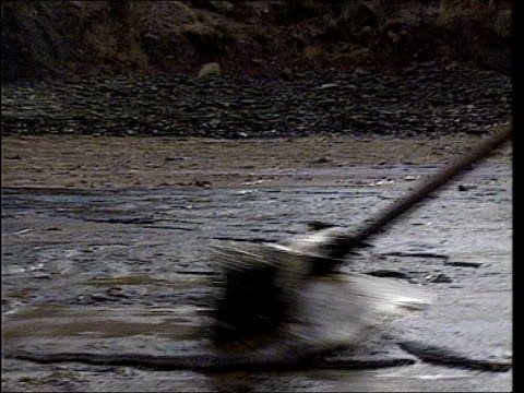 environmental disaster lib wales milford haven environmental workers cleaning up oil from shore - oil spill stock videos & royalty-free footage