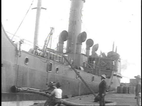 1923 ws oil tanker docked while longshoremen are loading a large hose onto deck / united states  - 1923 stock-videos und b-roll-filmmaterial