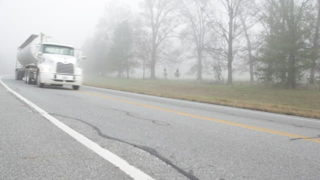 oil tanker on country road in dense foggy morning - articulated lorry stock videos & royalty-free footage