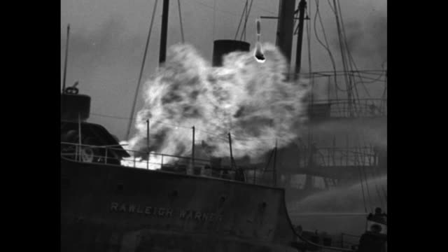 VS oil tanker Rawleigh Warner's deck afire with men on fireboat spraying water nighttime view of entire boat burning on the Mississippi River