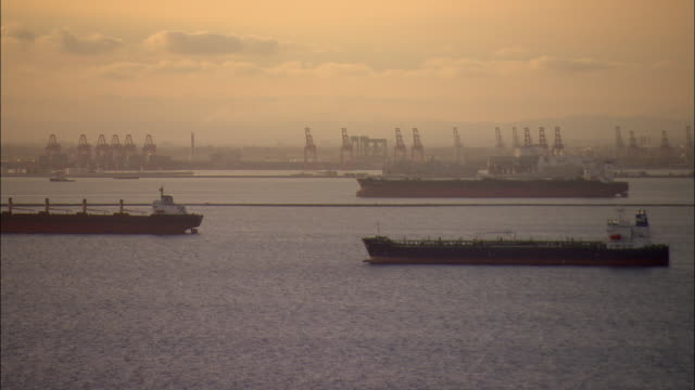AERIAL Oil tankers anchored off Port of Long Beach at sunset, California, USA