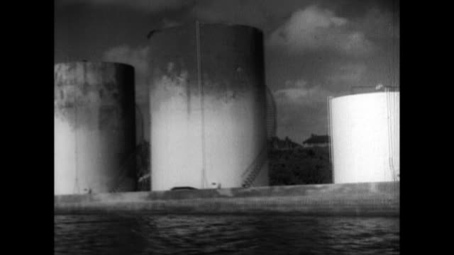 Oil tanks port facilities and urban areas dot coastal Guam under Japanese occupation during World War II a display features a US submarine torpedo a...
