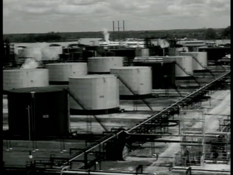 vidéos et rushes de oil tower & tanks on hill. oil refinery w/ rows of tanks. two round oil storage tanks. two men talking w/ paper pointing. oil refinery w/ smoke... - 1942
