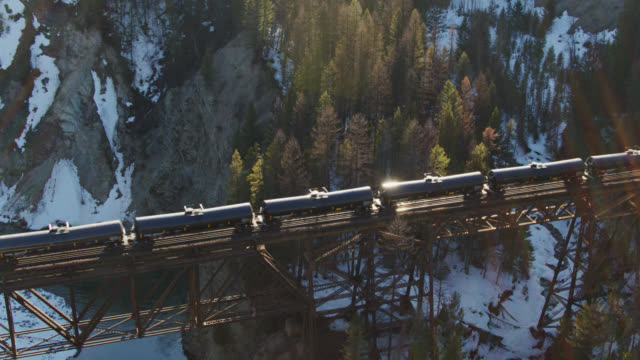 oil train crossing bridge in rocky mountains in winter - aerial - rail transportation stock videos & royalty-free footage