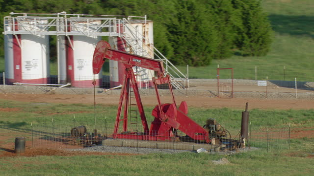 vidéos et rushes de oil well and storage tanks in oklahoma - tour de forage