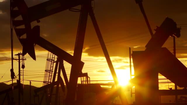 oil well piston pumps at sunset - ドラム容器点の映像素材/bロール