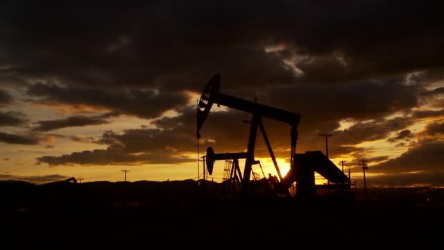 oil well piston pumps at sunset - stahlfass stock-videos und b-roll-filmmaterial