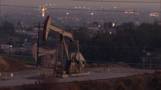 WS HA Oil well pump jack on hill at dusk, illuminated cityscape in background / Los Angeles, California, USA