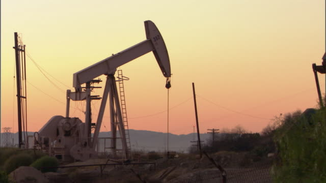 WS Oil well pump jacks against sky at sunset / Los Angeles, California, USA
