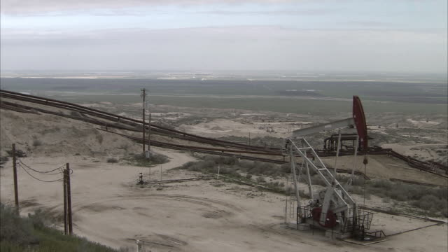 pan oil well pumping oil with oil pipelines running downhill / bakersfield, california, united states - pipeline stock videos and b-roll footage