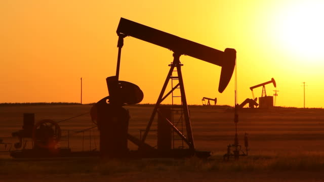 oil wells pumping at sunset - pipeline stock videos and b-roll footage