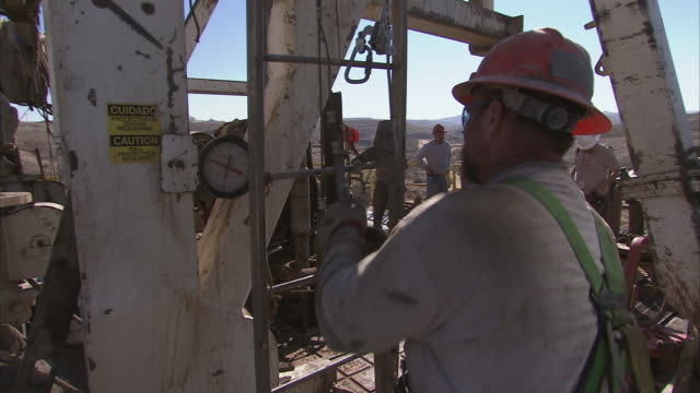 ts oil worker wearing a hard hat attaching his safety harness and climbing up a ladder on an oil platform / bakersfield, california, united states - wrench stock videos and b-roll footage