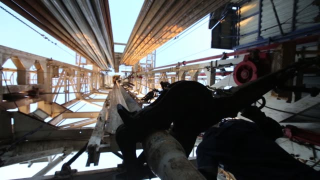 vídeos de stock, filmes e b-roll de oil workers arrange drilling pipe sections at the turntable on an oil drilling platform operated by tatneft oao near almetyevsk russia on friday july... - poço de petróleo