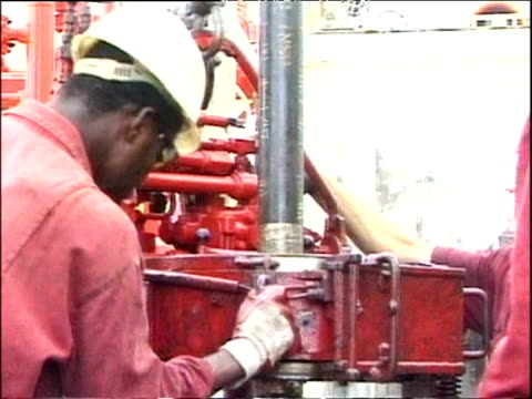 oil workers guiding extraction mechanism on offshore oil platform africa - struggle stock videos and b-roll footage