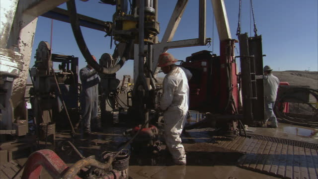 stockvideo's en b-roll-footage met ms oil workers in protective clothing clean around the base of an oil drill as a pipe lifts up / bakersfield, california, united states - olie industrie