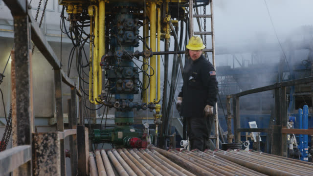 oilfield workers rig up drilling pipe on a tall, metal platform at an oil and gas drilling pad site on a cold, winter morning - mining stock videos & royalty-free footage
