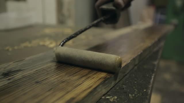 oiling a length of timber - トラッキングショット点の映像素材/bロール