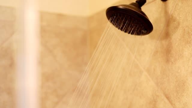 Öl-geriebener Bronze-Duschkopf mit fließendem Wasser im Badezimmer.