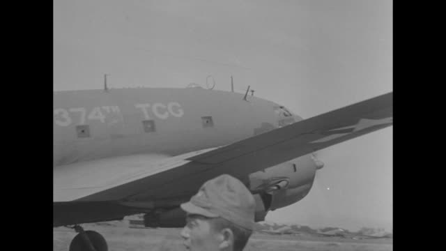 US soldiers in trucks on tarmac filled with Douglas C54 transport planes as preparations begin for military occupation of Japan after surrender in...