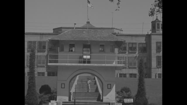 oklahoma state penitentiary topped with waving american flags armed guard atop crenelated wall semicircle portal into facility with stairs wall with... - 脱獄する点の映像素材/bロール