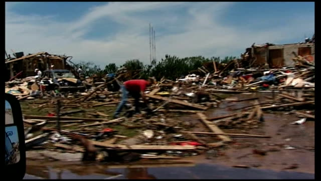funerals continue for those killed usa oklahoma shot from side of car of debris rubble and collapsed houses various shots people retrieving material... - oklahoma stock-videos und b-roll-filmmaterial