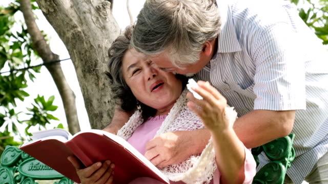 vídeos de stock, filmes e b-roll de velhice, aposentadoria e conceito de pessoas - mulher sênior feliz lendo livro sentado no banco no parque. um casal feliz e romântico da idade da reforma - old book