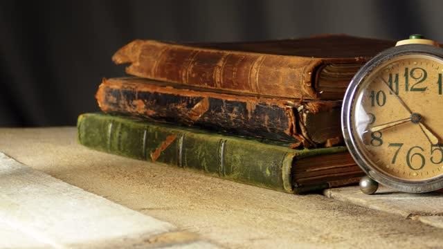 古い古代の革カバーブックと木製の背景にヴィンテージ時計 - 本棚点の映像素材/bロール