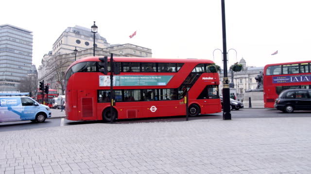 Old and new routemaster double decker red buses in London at Trafalgar square in slow motion