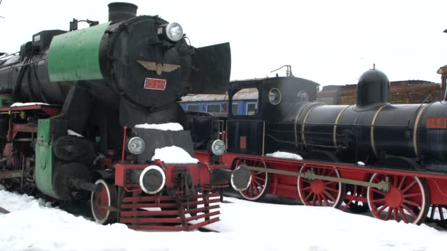 old and rusty steam locomotives with wagons in bad condition standing at ruse a railway station in bulgaria - wheel stock videos & royalty-free footage