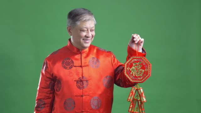 alten asiatischen mann in rote mandarin frohes neues jahr 4 k - gratulieren stock-videos und b-roll-filmmaterial