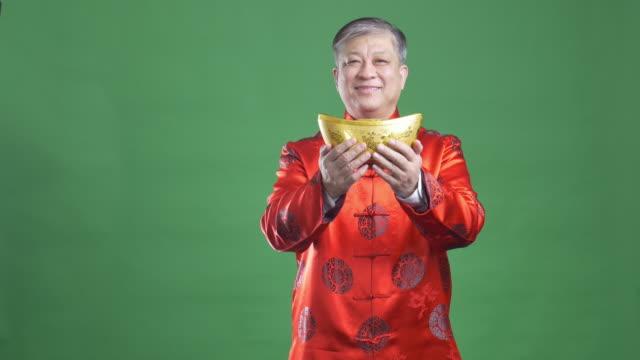 vídeos de stock, filmes e b-roll de velho homem asiático em vermelho mandarim feliz ano novo de 4 k - roupa tradicional