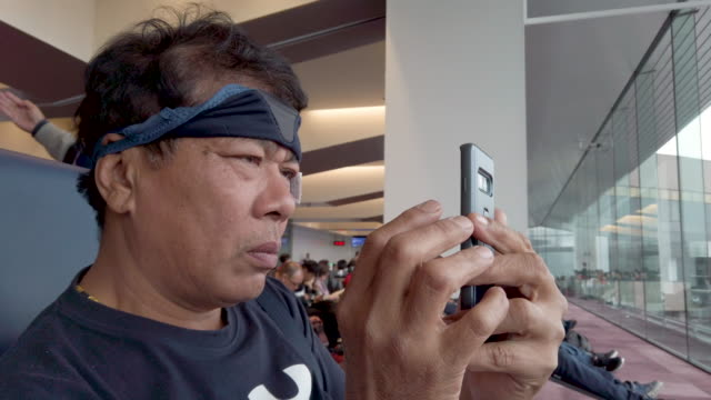 Old asian man with blindfold using smart phone in airport