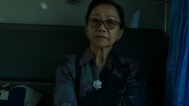 vídeos de stock, filmes e b-roll de mulher asiática idosa que viaja pelo trem - só uma mulher idosa