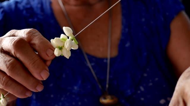 Old Asian women make jasmine garland